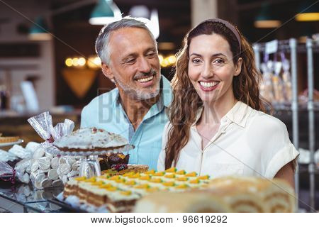 Cute couple looking at pastries in the bakery store