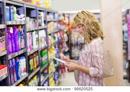 Side view of a pretty blonde woman writing on her notepad in supermarket