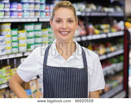 Portrait of a smiling blonde worker with hand on hip in supermarker