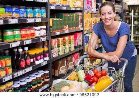 Pretty woman looking at camera and pushing trolley at supermarket