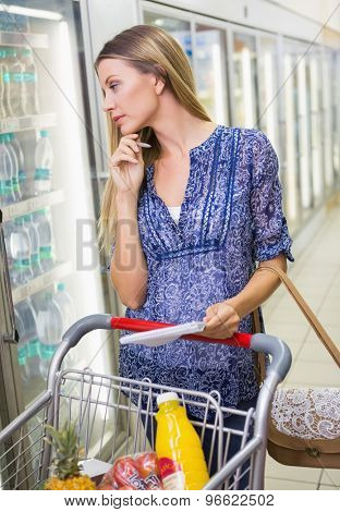 Portrait of a woman writing in his notepad in the frozen aisle in the supermarket