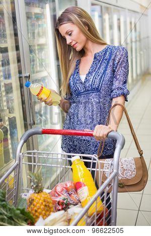 A pretty smiling blonde woman buying lemonade at supermarket