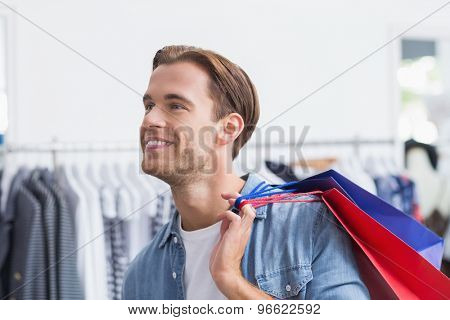 Portrait of a smiling man with shopping bags at the clothing store