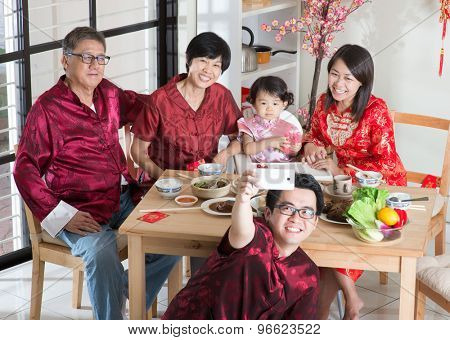 Chinese New Year celebration, reunion dinner. Happy Asian Chinese multi generation family with red cheongsam selfie while dining at home.