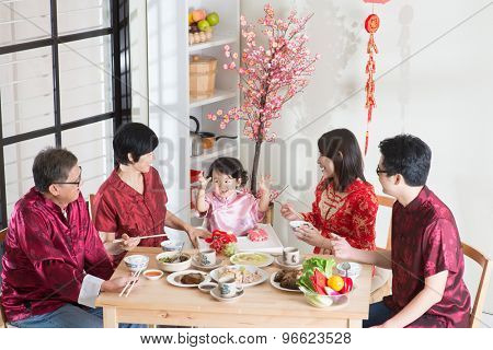 Celebrating Chinese New Year, reunion dinner. Happy Asian Chinese multi generation family with red cheongsam dining at home.