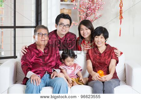 Chinese new year celebration. Happy Asian multi generations family in red cheongsam reunion at home.