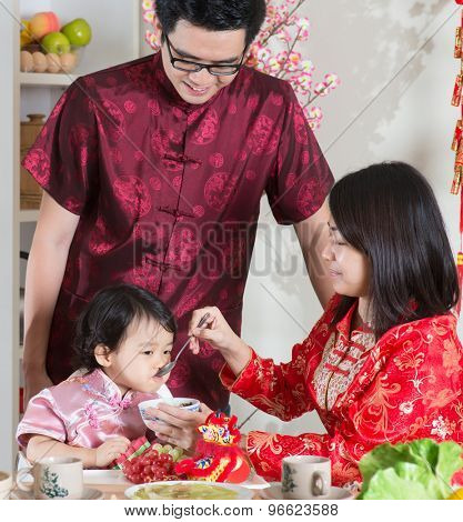 Chinese New Year, reunion dinner. Happy Asian Chinese family with red cheongsam dining at home.