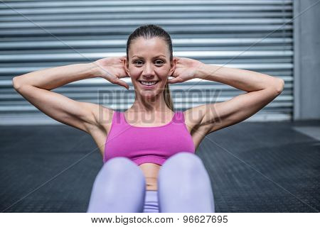 Portrait of a muscular woman doing abdominal crunch