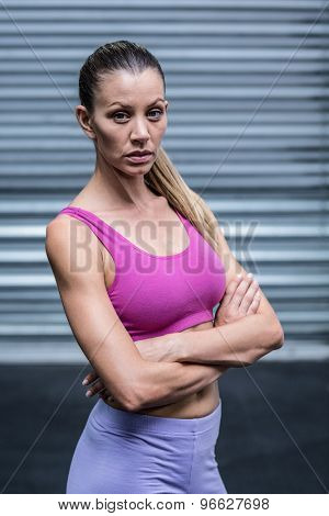 Portrait of a serious muscular woman with hands on hips