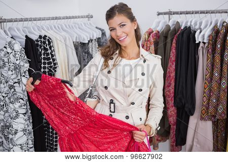 Portrait of smiling woman holding red dress and looking at camera at a boutique