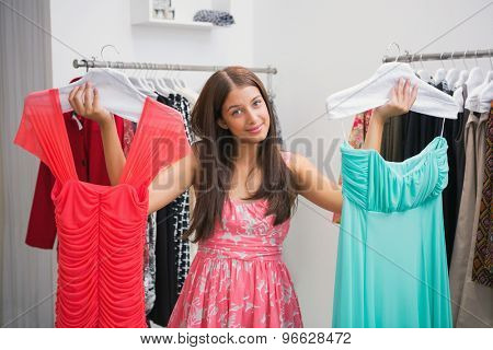 Portrait of woman having difficulties choosing dress at a boutique
