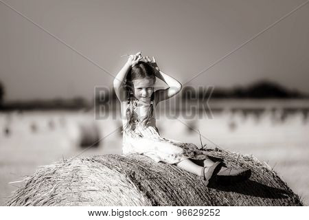 Funny Cute Little Girl Posing On The Haystack In Summer Field