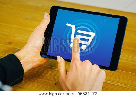 Businesswoman using tablet at desk against trolley
