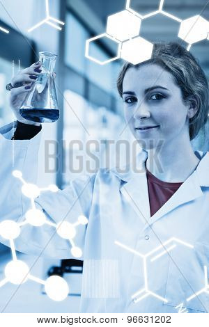Science graphic against portrait of a chemist holding a blue liquid