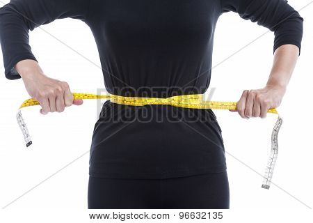 Weight Loss Concept, The Woman In Black Tries To Reduce Her Waist By Measuring Tape On White Backgro