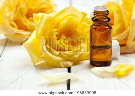 yellow roses and petals with bottle of aromatic essence