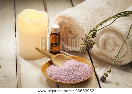 spa still life with lavender, bath salt, aromatic oil, candle and towels on wood background