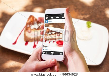 Hand holding smartphone against cheesecake with chantilly cream and coulis