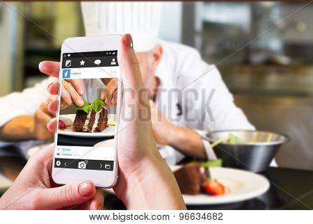 Hand holding smartphone against concentrated male pastry chef decorating dessert in kitchen