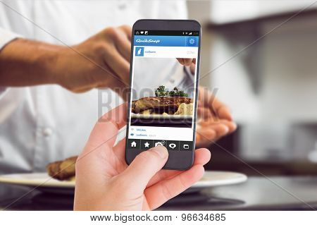 Female hand holding a smartphone against closeup mid section of a chef putting salt
