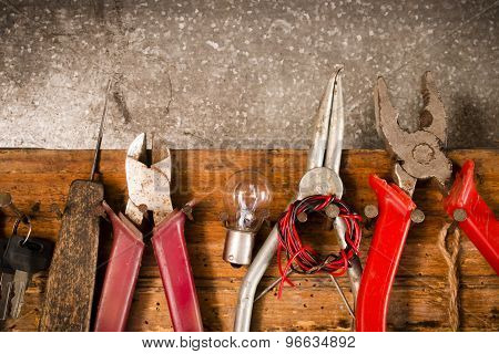 Wrenches, Pliers, Bulbs, Pliers, Wire, Rope On The Nails On The Old Wooden Stand