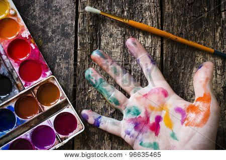 Watercolor Paint Brush To Paint The Hand Of The Artist In Multi-colored Paint On Wood Background