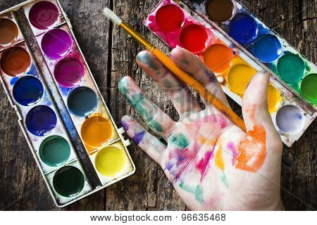 Watercolor Paint Brush To Paint The Hand Of The Artist In Multi-colored Paint On Wood Background Hol