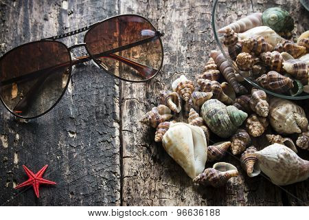 Glasses, Pours Seashells, Starfish On A Wooden Background Selective Focus