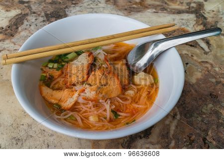 noodle with roasted red pork in the white bowl