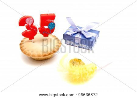 Cupcake With Thirty Five Years Birthday Candle, Whistle And Gift On White