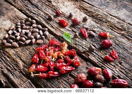The Heart Of The Dry Red Pepper, Pine Nuts, Dogrose On Wooden Background Side View Selective Focus