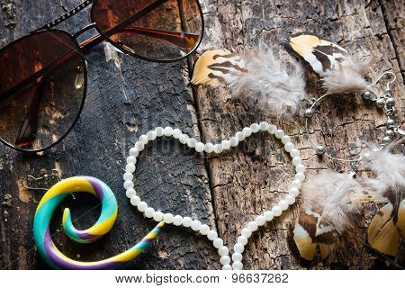 Glasses, Earrings With Feathers, Dreamcatcher, Jewelry, Beads In The Shape Of A Heart On A Wooden Ba