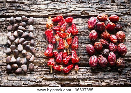 The Figure Of The Pine Nuts, Dry Red Pepper And Dogrose On A Wooden Background Selective Focus