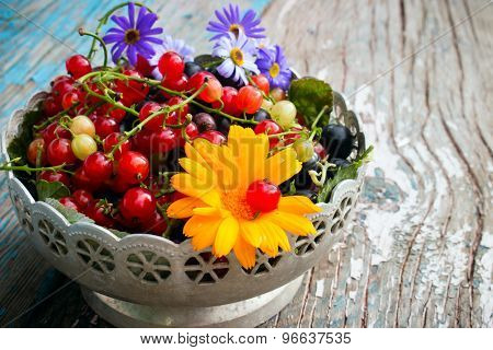 A Plate Of Leaves And Berries Of Black And Red Currant With A Flower On A Wooden Background
