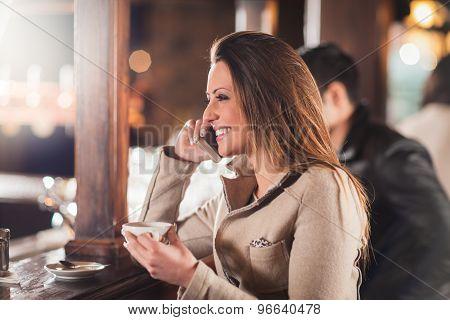 Smiling Woman At The Bar Having A Phone Call