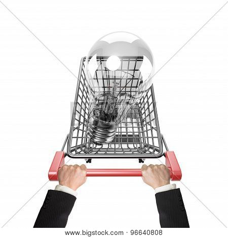 Hands Pushing Shopping Cart With Large Light Bulb