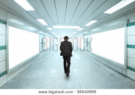 Rear View Businessman Walking Through Bright Underpass