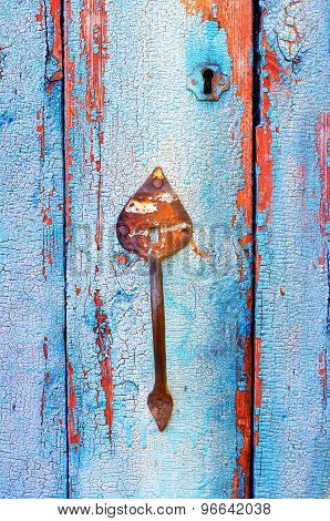 Old tacky blue door with vintage handle and keyhole, wooden texture