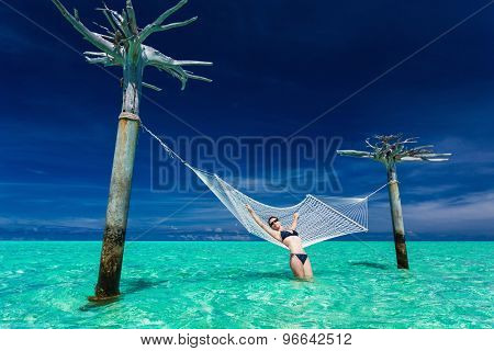 Woman relaxing on over-water hammock in the middle of tropical lagoon, Maldives