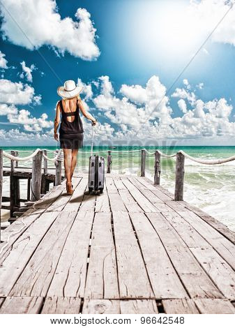 YOung female traveller walking on the wooden deck at tropical beach