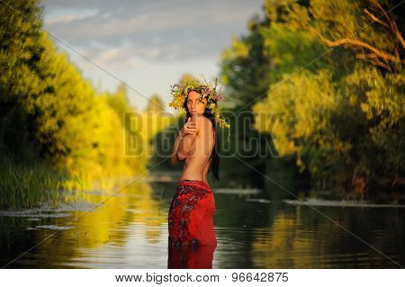 Topless Long-haired Brunette Girl In Red Skirt And Grass Wreath Standing In Shallow River At Sunset