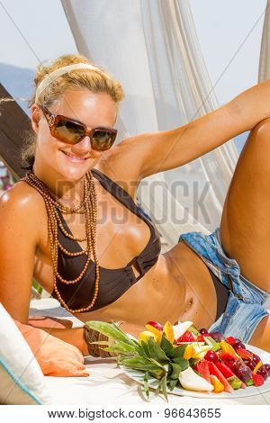 Beautiful young woman at the summer lounge eating a fruit salad