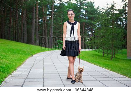 Happy Teenage Girl Walking With Dog Yorkshire Terrier In Park