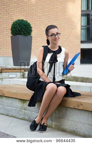 Smiling Teenage Girl In School Uniform Sitting On Bench