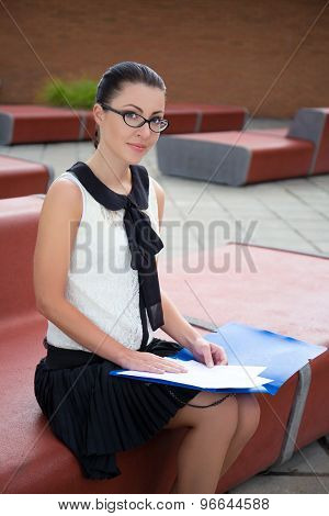 Portrait Of Teenage Girl Sitting On Bench And Reading Something