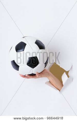 Hand break through paper with soccer ball