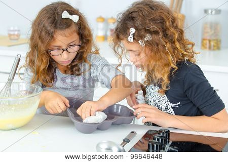Children cleaning cake mold