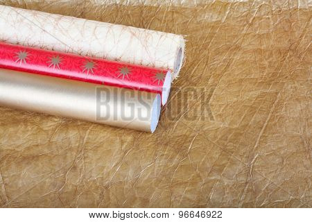 Rolls Of Multicolored Wrapping Paper With Streamer For Gifts On Gold Abstract Background