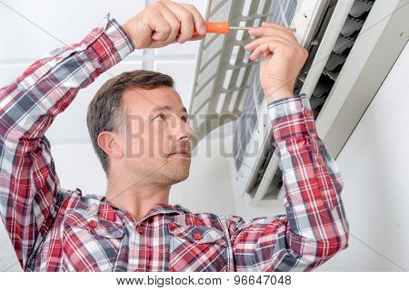 Man repairing air conditioning unit