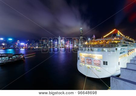 Illuminated Cruise ship and panoramic skyline of hong kong